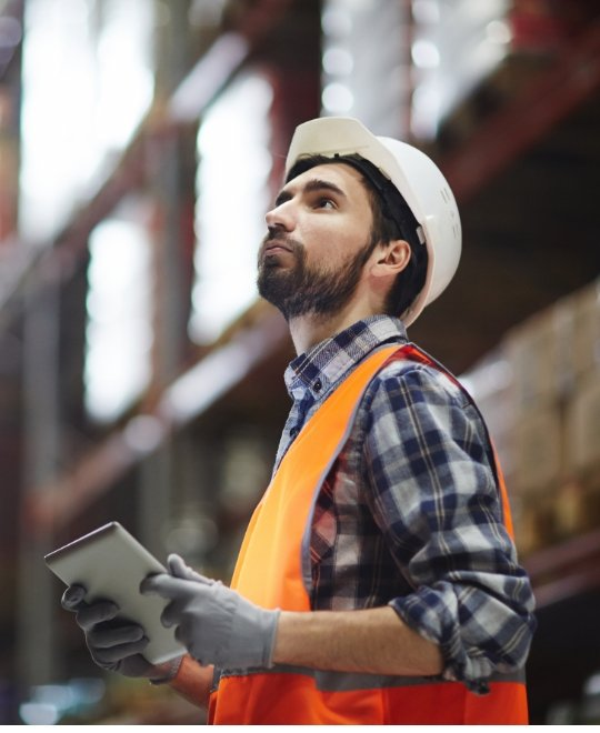man with safety helmet and vest holding tablet looking up