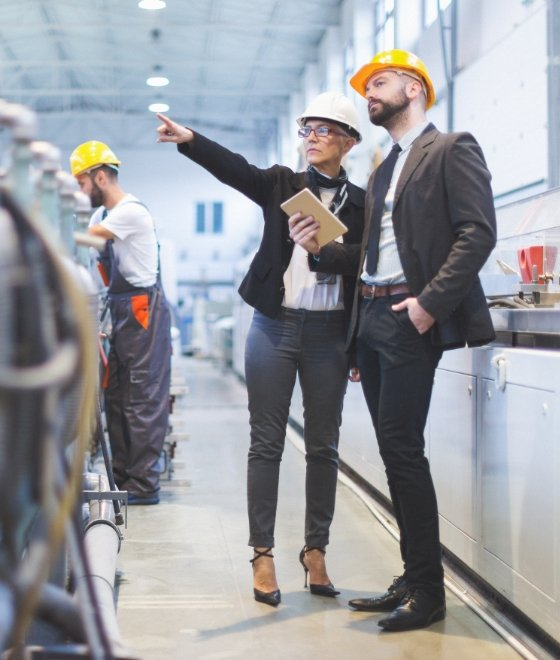 man and woman with safety helmets on standing in workplace pointing left