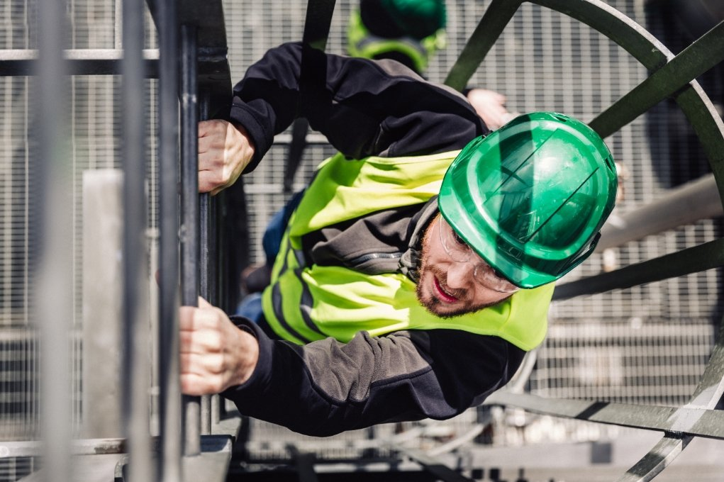 man with safety helmet and vest climbing a fire exit